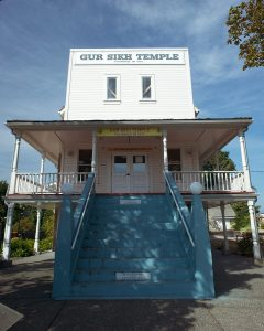 "White false-front 3-storey building with blue concrete stairs to the front door on the second storey. Sign on the top of the false front reads ""Gur Sikh Temple built 1911""."