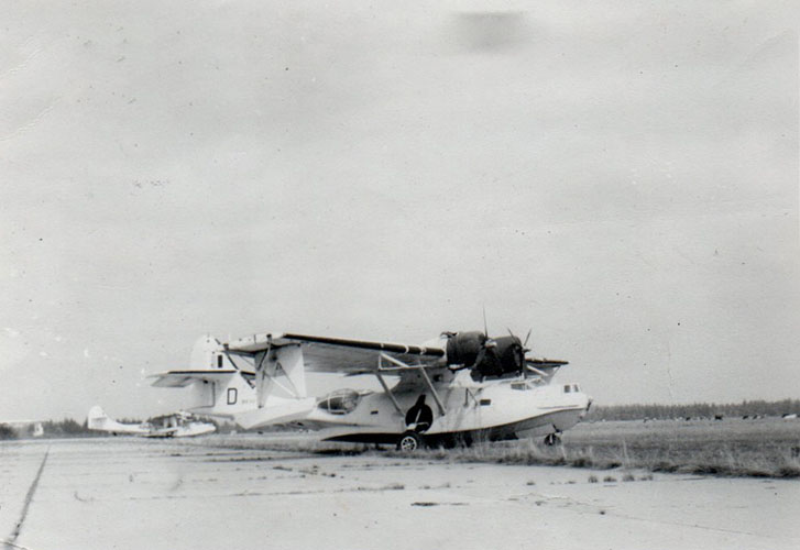 Black and white photo of two planes on a tarmac.